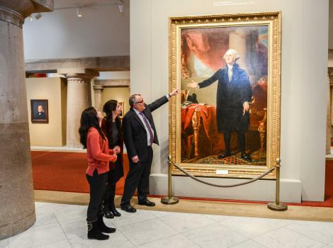 Picture of a man pointing towards a painted full-length portrait of George Washington