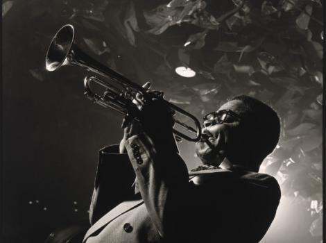 Black and white photograph of a man playing a trumpet