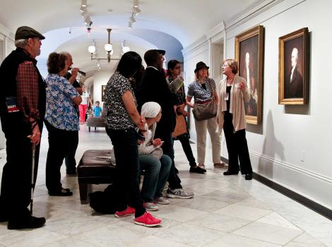 A group of people gathered around a portrait listen to a woman pointing to the wall