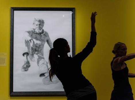 Silhouette of women dancing against a yellow wall with a portrait on it