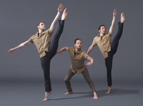 Image of three men dancing in a line