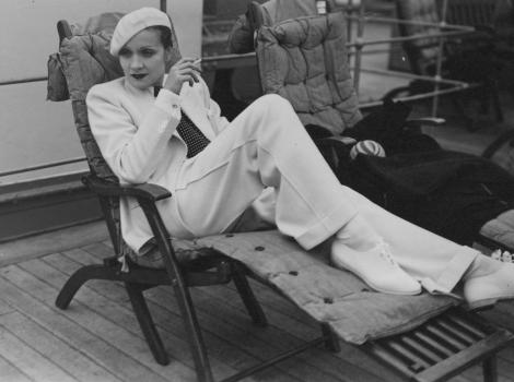 Black and white photograph of a woman smoking on a chaise lounge