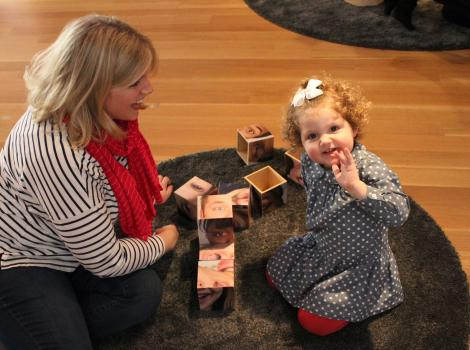 A mother and daughter sitting on the floor and playing with blocks