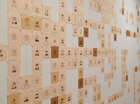 Photograph of many flesh-colored drawings tacked to a white wall