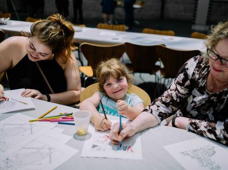 Photograph of two woman and a small girl coloring at a table and smiling
