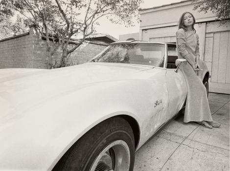 A black and white image of a woman leaning against a car