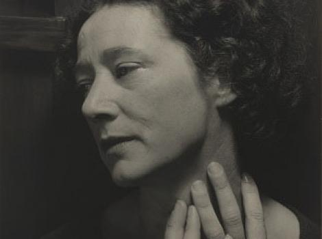 Sepia tone photograph of a woman with her hands on her neck