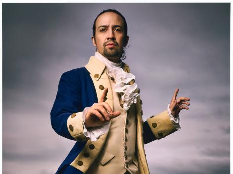A man wearing colonial clothes and pointing at the camera