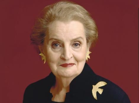 A photograph of a woman staring at the viewer wearing a black suit and a dove pin