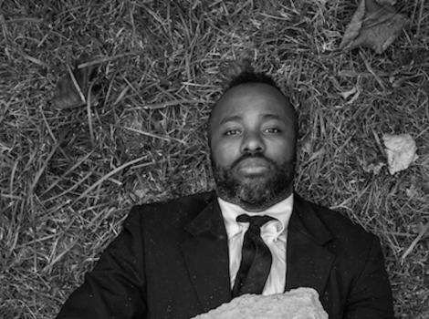 Black and white photo of a man buried under a rock and staring at the camera