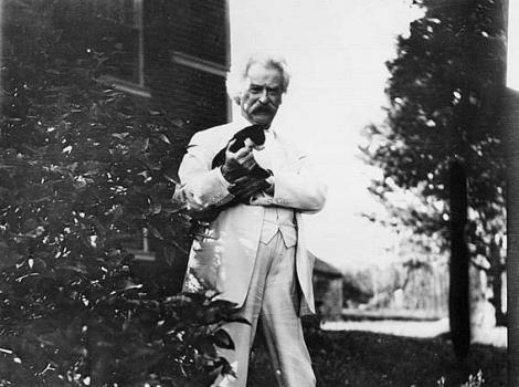 Black and white photograph of a man in a white suit petting a very small kitten