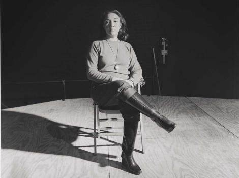 Black and white photo of a woman sitting cross-legged on a chair in the middle of a stage
