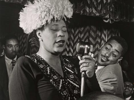 Black and white image of a woman singing into a microphone and wearing a hat