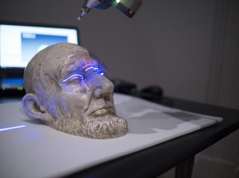 Small white plaster cast of a bearded man's face is scanned by a large laser that casts a blue light