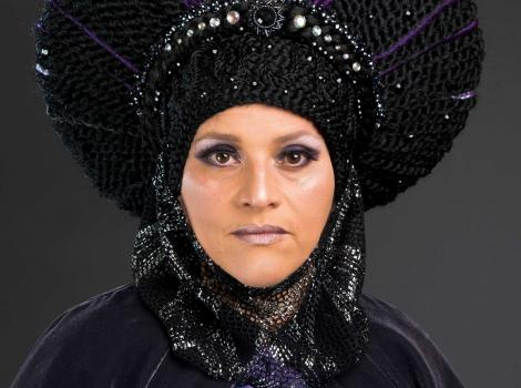 A head shot of a woman wearing a purple robe and headdress looking straight into the camera