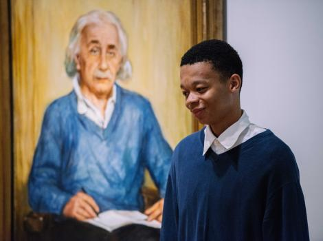 Photograph of a girl in a blue shirt standing in front of a painting of Albert Einstein, who is also wearing a blue shirt