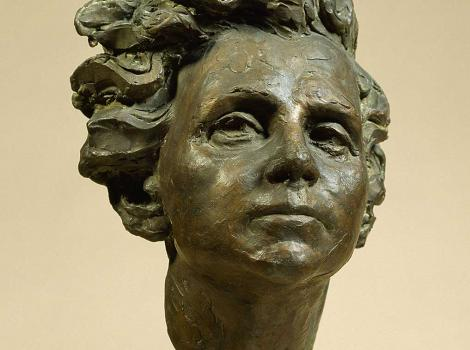 A bronze bust of a woman with flowing hair set on a marble slab