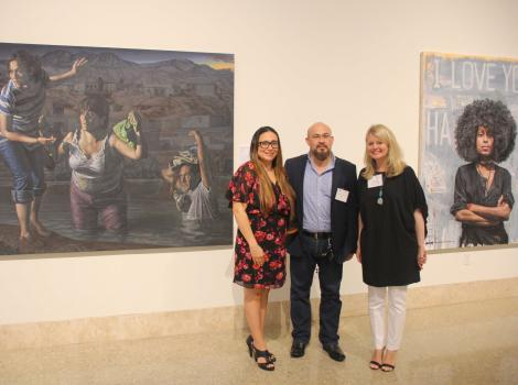 Three women standing in front of a painting