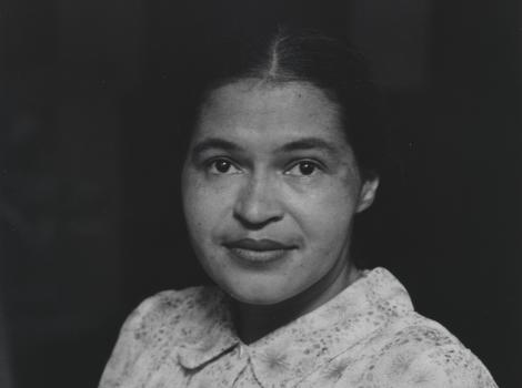 Black and white image of woman wearing white dress and smiling softly