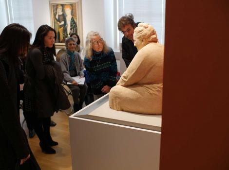 A group of people closely examining a sculpture in a museum gallery