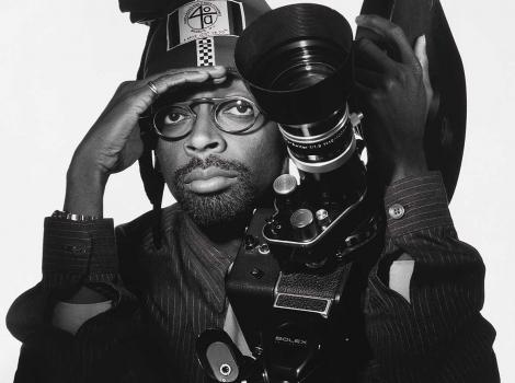 Black and white photograph of a man staring at the viewer with his face behind a camera