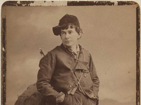 A sepia toned old photograph of a young man leaning against a rock