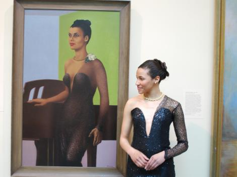 Woman dressed in black dress stands in front of a portrait and looks to the left