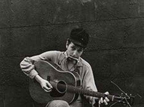 Young man playing guitar and a harmonica