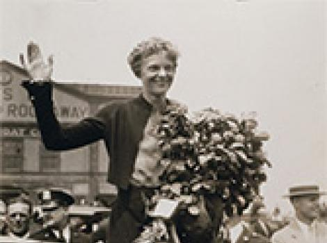 Amelia Earhart waving to a crowd