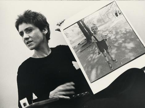 Woman holding a large photograph of a child