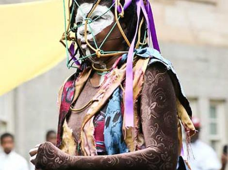 Woman in colorful clothing with wire cage over her face and facial paint