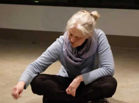 Sarah Huckleberry sitting cross legged on floor and arranging small sticks of wood