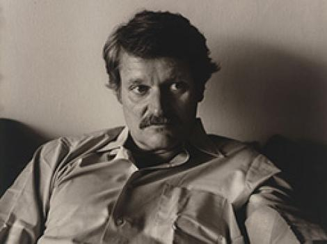 Seated man with dark hair and a moustache