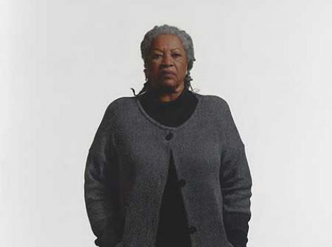 African American woman in a dark sweater standing against a white background