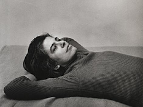 Susan Sontag lying on a bed with her hands behind her head