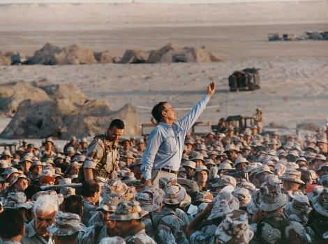 George H.W. Bush amidst a crown of soldiers in Saudi Arabia