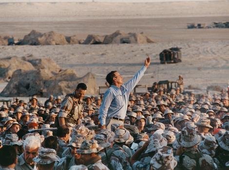 George H.W. Bush amidst a crown of soldiers in Saudi Arabia