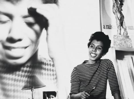 woman standing next to a large photo of herself