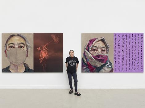 Woman standing between two self-portraits in a studio