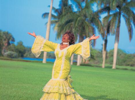 Woman in a long yellow dress with ther arms outstretched