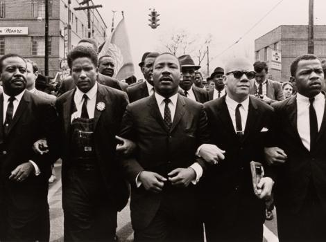 group of men marching arm in arm