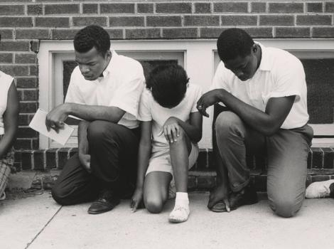 Group of African Americans praying on a sidewalk
