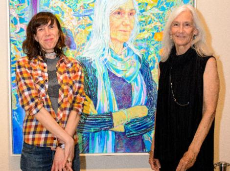 Two women standing in front of a portrait