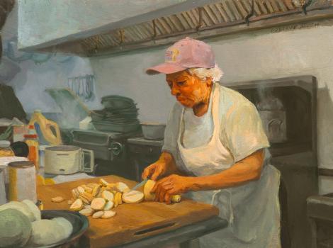 Woman in a kitchen cutting squash
