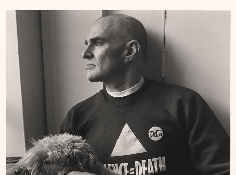 Profile portrait of a man in a sweatshirt with his dog