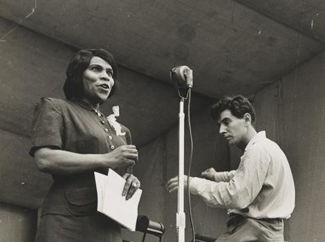woman singing at a microphone and a seated man conducting