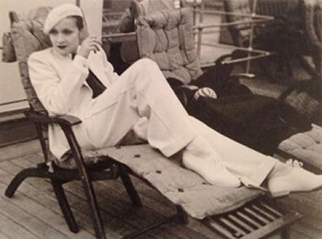 Wonam in a white pantsuit and white beret on a chaise lounge