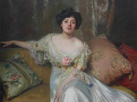 19th century woman in a white gown on a pillowed couch