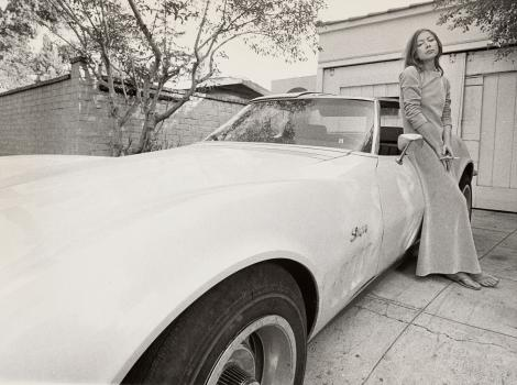 Woman in a long dress standing by a Camero