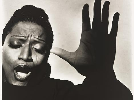 Woman singing with her hand beside her face